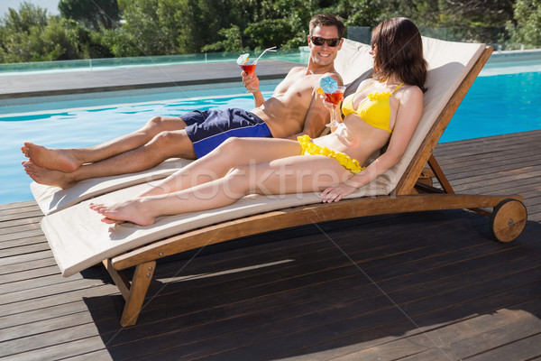 Couple with drinks sitting by swimming pool Stock photo © wavebreak_media