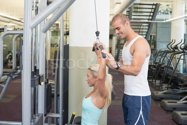 Trainer assisting young woman on a lat machine in gym Stock photo © wavebreak_media