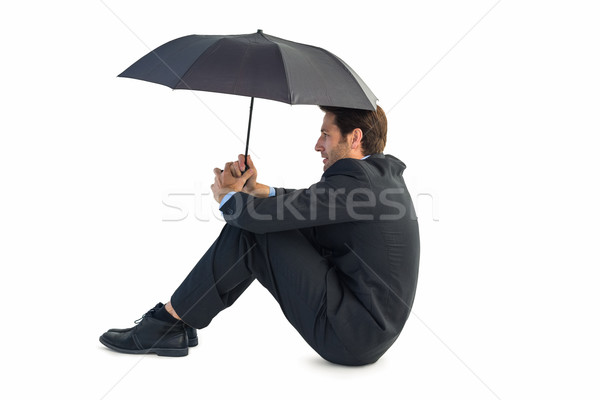 Businessman holding umbrella sitting on the floor Stock photo © wavebreak_media