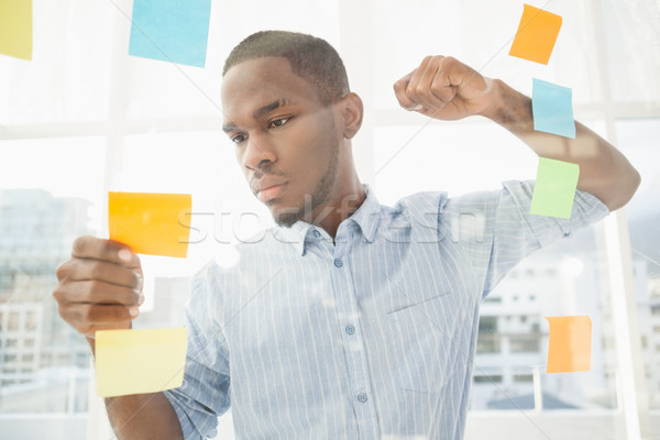 Focused businessman reading sticky notes  Stock photo © wavebreak_media