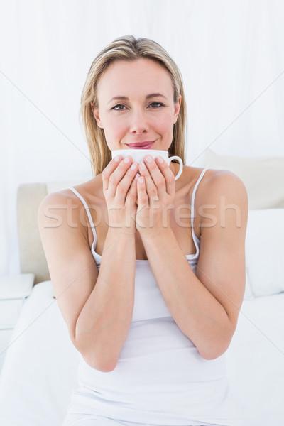 Gülen sarışın oturma yatak kupa Stok fotoğraf © wavebreak_media