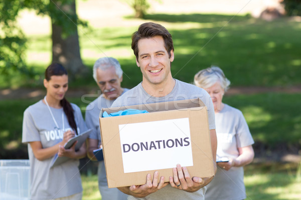 Happy volunteer man holding donation box Stock photo © wavebreak_media