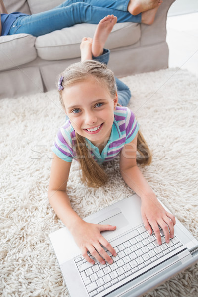 Portrait of happy girl using laptop while lying on rug Stock photo © wavebreak_media
