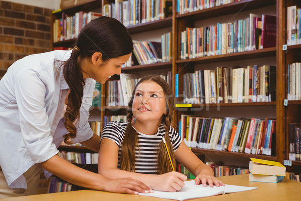 Teacher assisting girl with homework in library Stock photo © wavebreak_media