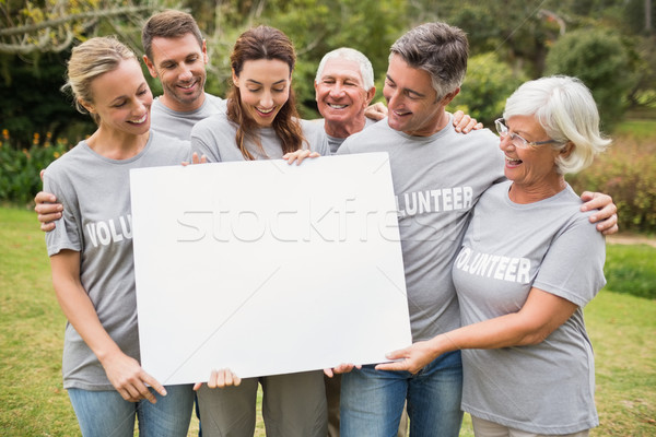 Happy volunteer family holding a blank  Stock photo © wavebreak_media