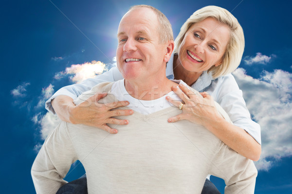 Stock photo: Composite image of happy mature man giving piggy back to partner