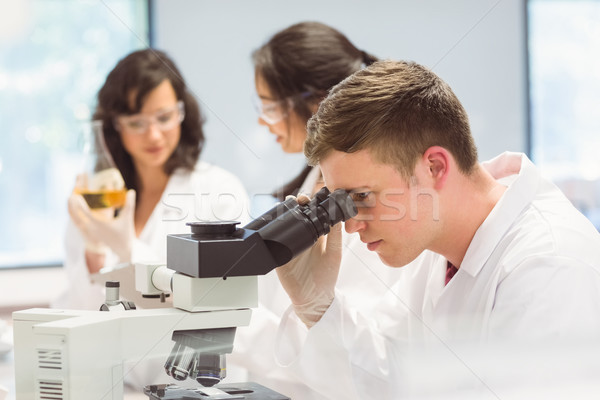 Science student looking through microscope in the lab Stock photo © wavebreak_media