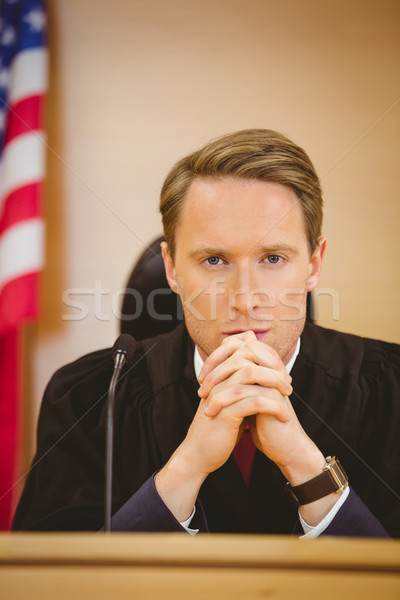 Stock photo: Unsmiling judge with american flag behind him