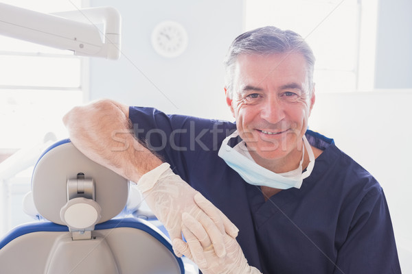 Smiling dentist leaning against dentists chair  Stock photo © wavebreak_media