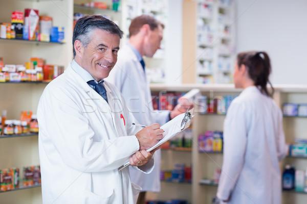 Mosolyog gyógyszerész laborköpeny ír recept gyógyszertár Stock fotó © wavebreak_media