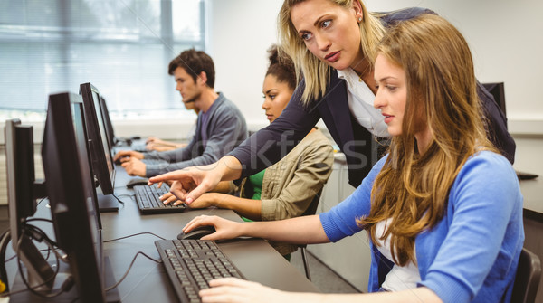 Attractive teacher helping her student in computer class Stock photo © wavebreak_media