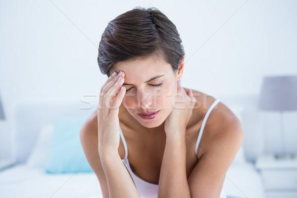 Beautiful brunette suffering from head ache  Stock photo © wavebreak_media