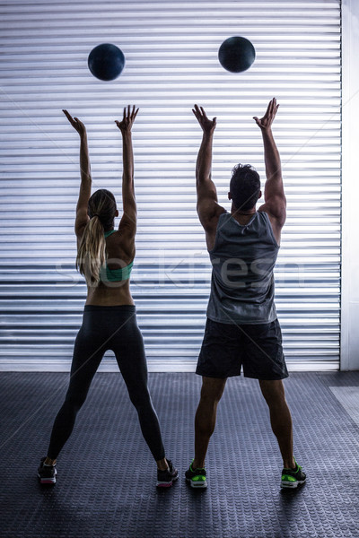 Muscular couple throwing ball in the air Stock photo © wavebreak_media