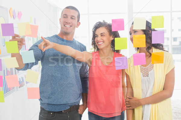 Smiling coworkers pointing sticky notes Stock photo © wavebreak_media