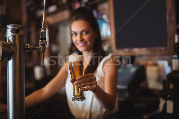 Female bar tender holding glass of beer Stock photo © wavebreak_media