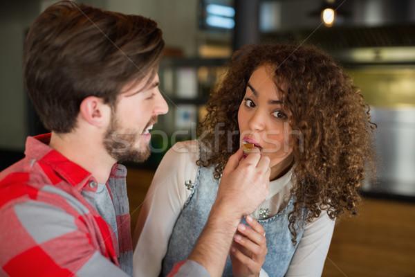 Smiling man feeding cake to woman during celebration Stock photo © wavebreak_media