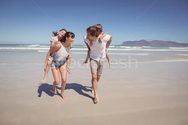 Happy parents piggybacking their children at beach Stock photo © wavebreak_media