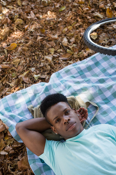 Young man relaxing on a picnic blanket Stock photo © wavebreak_media