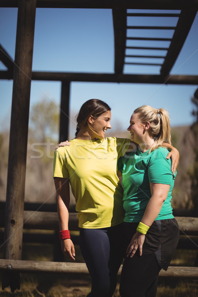 Happy friends standing with arms around during obstacle course Stock photo © wavebreak_media