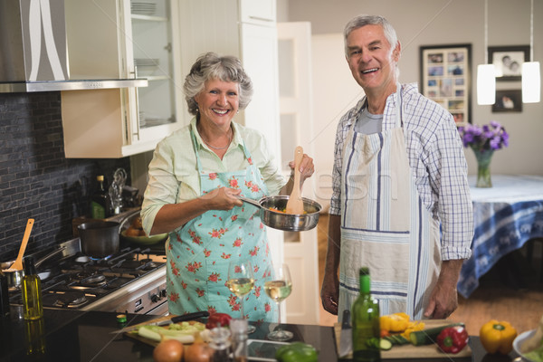 Cheerful senior couple cooking in kitchen at home Stock photo © wavebreak_media