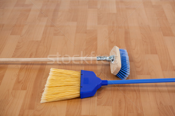 Two sweeping brooms on wooden floor Stock photo © wavebreak_media