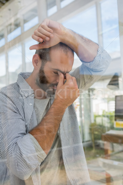 Tensed designer leaning seen through glass Stock photo © wavebreak_media
