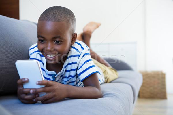 Sorridere ragazzo cellulare divano home soggiorno Foto d'archivio © wavebreak_media