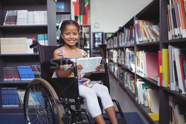 Girl on wheelchair smiling while holding digital tablet Stock photo © wavebreak_media