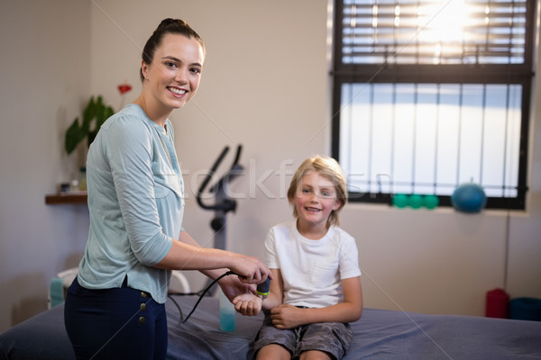 Stock photo: Portrait of smiling boy with female therapist scanning wrist