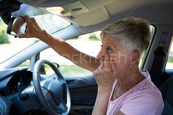 Senior vrouw naar achteraanzicht spiegel rijden Stockfoto © wavebreak_media