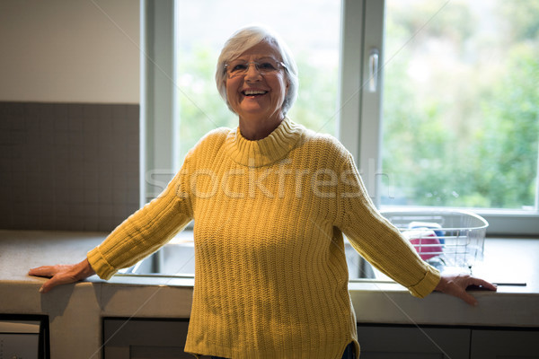 Smiling senior woman standing near kitchen worktop Stock photo © wavebreak_media