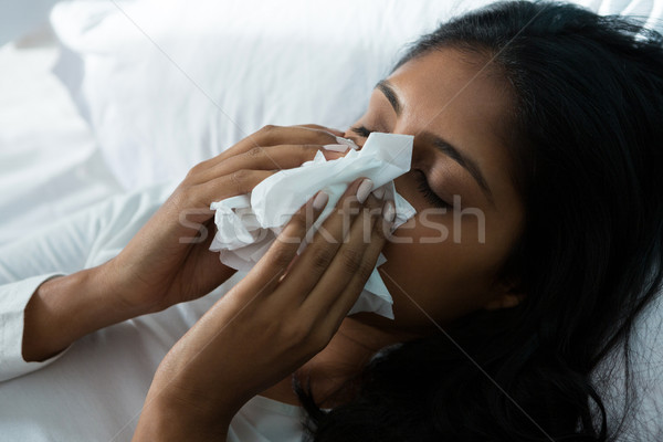 Woman blowing nose on bed Stock photo © wavebreak_media