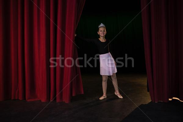 Smiling ballet dancer peeking through a stage curtain Stock photo © wavebreak_media