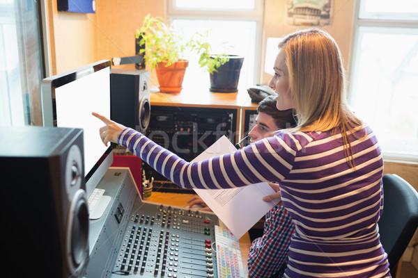Female employee explaining male radio host on monitor Stock photo © wavebreak_media