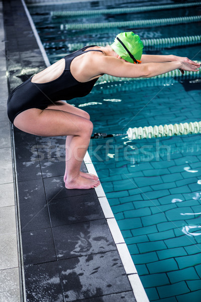 Swimmer woman about to dive into swimming pool Stock photo © wavebreak_media