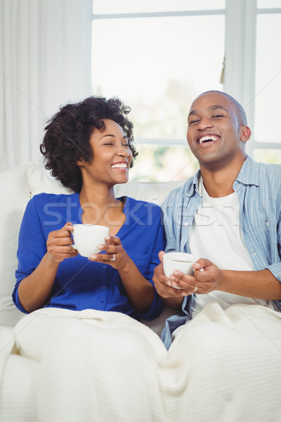 Happy couple holding cups on the sofa Stock photo © wavebreak_media