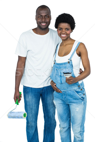 Pregnant couple holding a paint roller Stock photo © wavebreak_media
