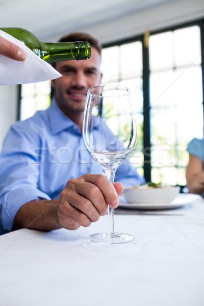 Waiter pouring wine in a glass of costumer Stock photo © wavebreak_media
