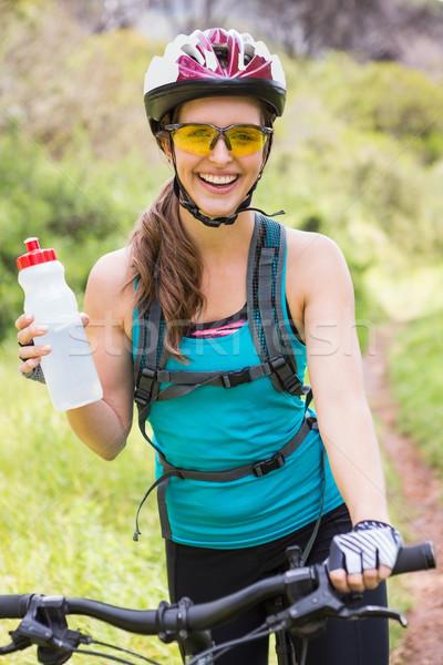 Uśmiechnięta kobieta stałego rowerów kobieta wody Zdjęcia stock © wavebreak_media