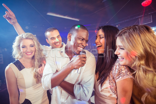 Heureux amis chanter karaoke night-club femme Photo stock © wavebreak_media