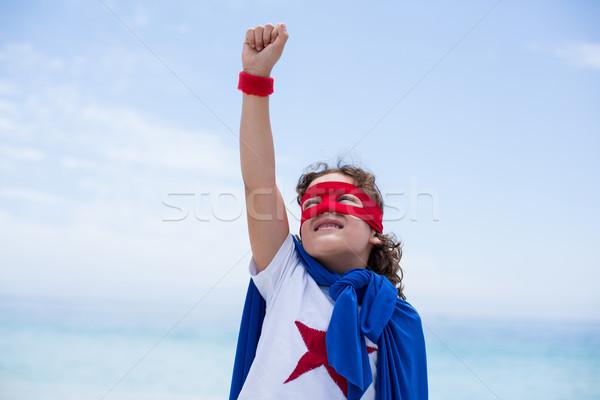 Boy in superhero costume with hand raised at beach Stock photo © wavebreak_media