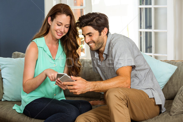 Couple looking at mobile phone and smiling Stock photo © wavebreak_media