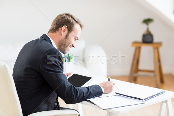 Businessman writing in a diary and using a digital tablet Stock photo © wavebreak_media