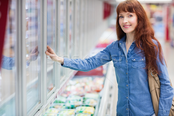 Woman smiling at camera while doing grocery shopping Stock photo © wavebreak_media