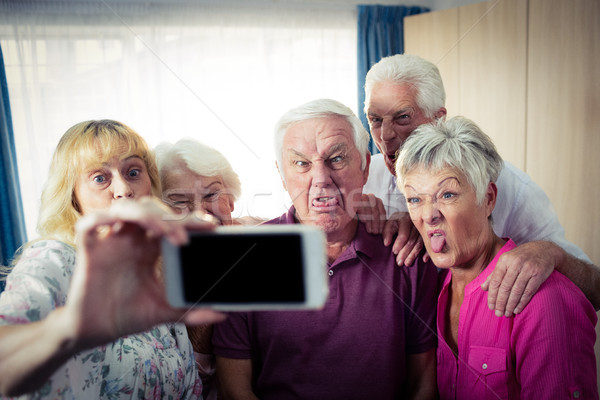 Group of seniors doing a selfie with a smartphone and funny face Stock photo © wavebreak_media