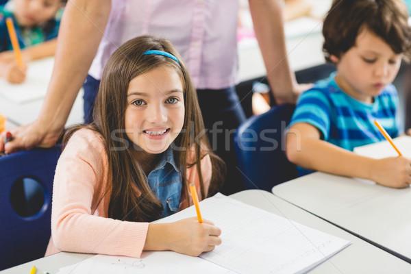 School girl doing homework in classroom Stock photo © wavebreak_media