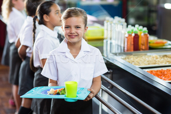 Cute schoolgirl with classmate standing near canteen counter Stock photo © wavebreak_media