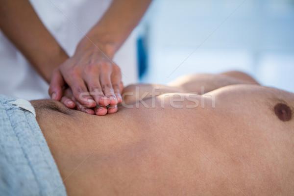 Physiotherapist giving stomach massage to a man Stock photo © wavebreak_media
