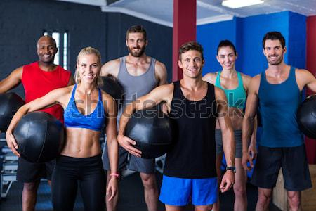 Portrait of cheerful fitness instructor with people in gym Stock photo © wavebreak_media