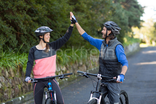 Biker couple giving high five while riding bicycle on the road Stock photo © wavebreak_media